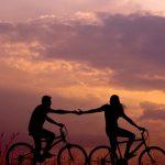 Couple on bikes in sunset