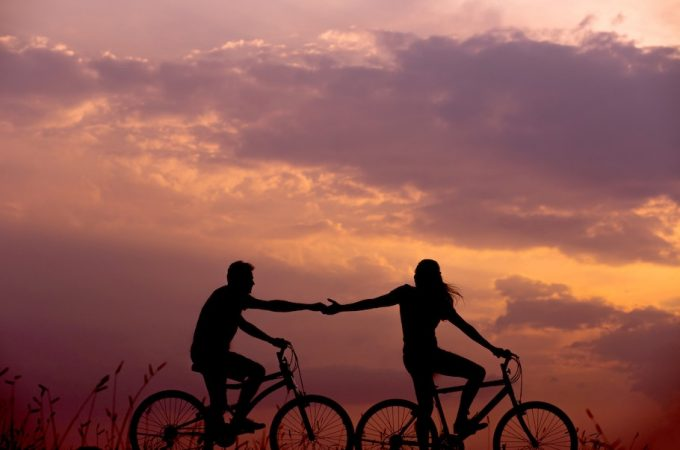 Couple on bikes in sunset