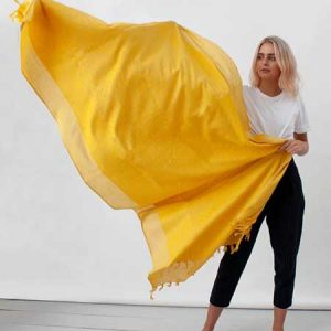 Buy her this Embroidered Scarf in Saffron is a natural cotton scarf dyed a bold saffron yellow with a matching embroidered panel and yellow tassels.